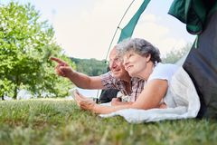 Senior couple on camping holiday. Senior couple camping in nature in tent with a tablet computer stock image