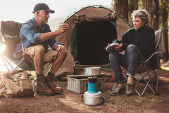 Senior couple camping in nature. Couple sitting at their campsite, with men drink coffee. Senior couple camping in nature stock photography
