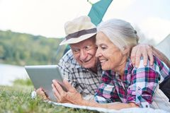 Senior couple camping is reading an email. Vital senior couple camping is looking forward to an email on the tablet computer stock images