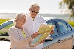 Senior couple with car looking for location on map. Road trip, travel and old people concept - senior couple with car looking for location on map in summer Stock Images