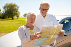 Senior couple at car looking for location on map. Road trip, travel and old people concept - senior couple at car looking for location on map in summer Stock Images