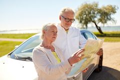 Senior couple at car looking for location on map. Road trip, travel and old people concept - senior couple at car looking for location on map in summer Stock Photo