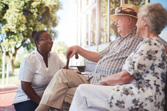 Senior couple with caregiver sitting outside Royalty Free Stock Image