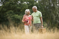A senior couple carrying a blanket and a picnic basket Stock Photo