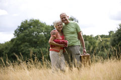 A senior couple carrying a blanket and a picnic basket Royalty Free Stock Image