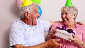 Senior couple celebrating a birthday on the couch stock footage