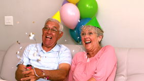 Senior couple celebrating a birthday on the couch. In slow motion stock footage
