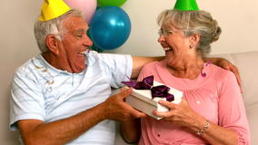 Senior couple celebrating a birthday on the couch. In slow motion stock video
