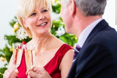 Senior couple celebrating Christmas with champagne Royalty Free Stock Images