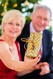 Senior couple celebrating Christmas eve Stock Images
