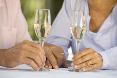 A senior couple celebrating close-up of hands and champagne flutes Royalty Free Stock Photo
