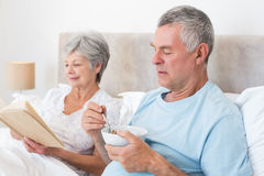 Senior couple with cereal bowl and book Stock Photos