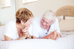 Senior couple chatting. Happy senior couple chatting on bed stock images
