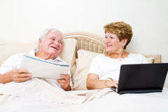 Senior couple chatting in bed Stock Images