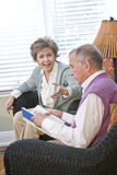 Senior couple chatting in living room reading book Royalty Free Stock Photo