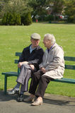 Senior couple chatting on park bench. A senior couple sitting having a chat on a park bench Royalty Free Stock Image