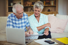 Senior couple checking bills in living room Royalty Free Stock Photography