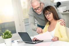Senior couple checking financial document, light effect. Senior couple checking financial document at home, light effect stock images