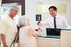Senior Couple Checking In At Hotel Reception Stock Photos