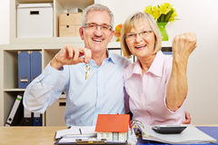Senior couple cheering with house and keys Royalty Free Stock Image
