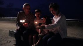 Senior couple and children having fun with sparklers stock video footage