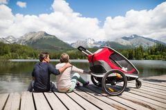 Senior couple with jogging stroller, summer day. Senior couple and children in jogging stroller, summer day. High mountains in the background. Rear view Royalty Free Stock Image