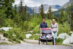 Senior couple and children in jogging stroller, summer day. Stock Photo