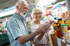 Senior family couple choosing bio food fruit and vegetable on the market during weekly shopping stock photo