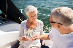 Senior couple clinking glasses on boat or yacht. Sailing, age, travel, holidays and people concept - happy senior couple clinking champagne glasses on sail boat Stock Images