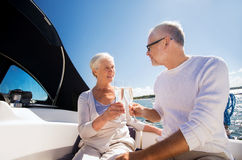 Senior couple clinking glasses on boat or yacht. Sailing, age, travel, holidays and people concept - happy senior couple clinking champagne glasses on sail boat Stock Photo