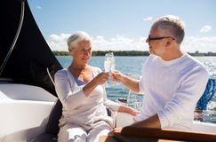 Senior couple clinking glasses on boat or yacht. Sailing, age, travel, holidays and people concept - happy senior couple clinking champagne glasses on sail boat Royalty Free Stock Images