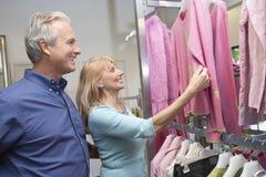 Senior Couple In Clothing Store. Happy senior couple looking at clothes in clothing store Royalty Free Stock Photography