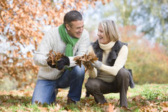 Senior couple collecting autumn leaves Stock Image