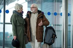 Senior couple are communicating with pleasure near air terminal. Enjoyable talk. Optimistic gray-haired men and women are standing near airport and enjoying Stock Photography
