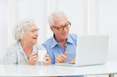 Senior couple with computer. Happy smiling retired couple using computer laptop at home Royalty Free Stock Image