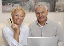 Senior couple computer. Portrait of a senior couple shopping and using computer laptop at home Stock Images
