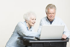 Senior couple on computer. Senior couple looking at computer screen happy Royalty Free Stock Photography