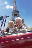 Senior couple in convertible driving by Eiffel Tower replica Royalty Free Stock Photo