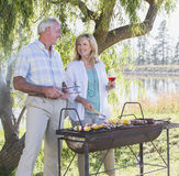 Senior Couple Cooking Barbeque In Countryside stock photography