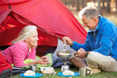 Senior Couple Cooking Breakfast On Camping Holiday Royalty Free Stock Images