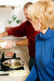 Senior couple cooking dishes in kitchen Royalty Free Stock Photography