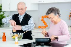 Senior couple cooking and having fun in kitchen Stock Photos