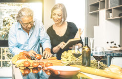 Senior couple cooking healthy food and drinking red wine Stock Image