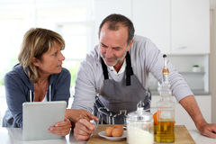 Senior couple cooking in the kitchen using tablet Royalty Free Stock Image