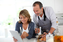 Senior couple cooking with tablet in the kitchen Stock Images