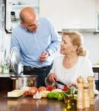 Senior couple cooking at their kitchen Stock Image