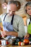 Senior couple cooking together in kitchen Royalty Free Stock Images