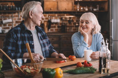 Senior couple cooking together at kitchen table Royalty Free Stock Photos