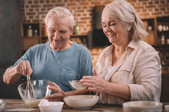 Senior couple cooking together at kitchen table Royalty Free Stock Photo