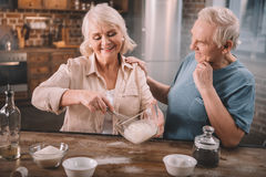 Senior couple cooking together at kitchen table Royalty Free Stock Images